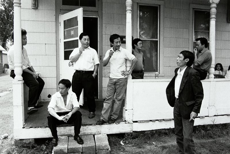 black and white photo of seven men on porch; '614' on door
