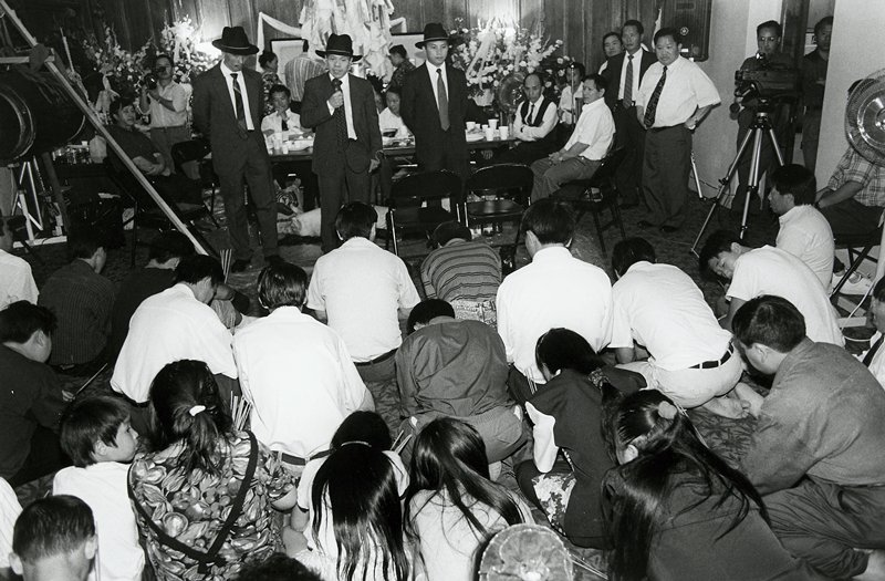 black and white photo of three men in hats addressing people kneeling on floor
