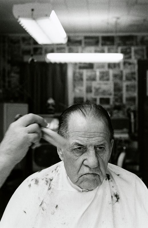 black and white photo of man with hair combed back; hand with brush LLQ