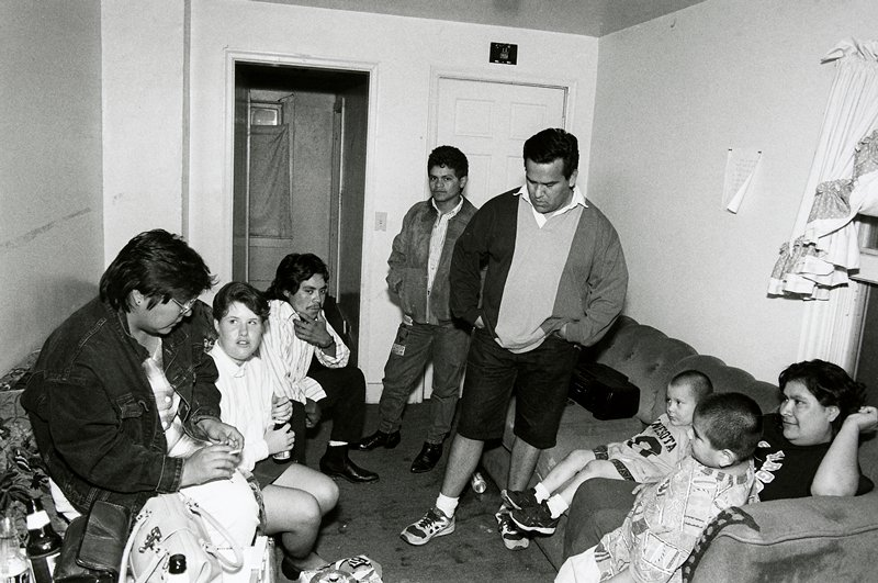 black and white photo of group of people in room, two men standing center