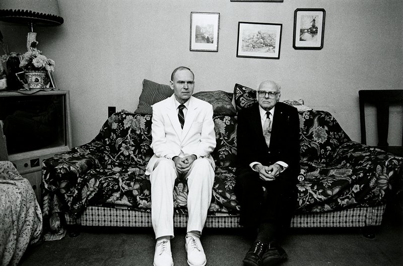 black and white photo of two men on couch; one in white suit, one in dark suit