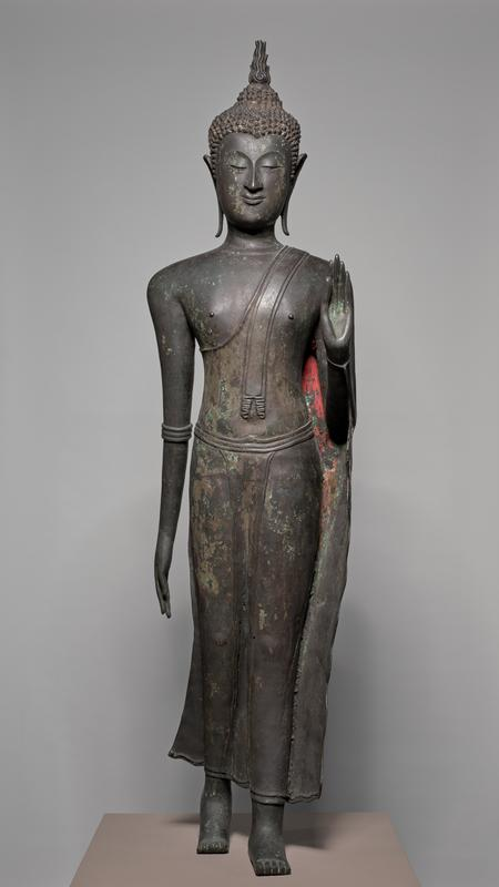 Buddha, bronze figure of, Marching. The figure, in marching position, is stiffle erect, the left foot forward; the left arm is bent at the elbow, the hand raised, palm outward; the right arm, braceleted at the elbow, is down. The ears are weighted, without earrings, and the hair, composed of small, spiky curls, is surmounted by a flame. Some of his features, which display the supernatural anatomy of Buddha, include projecting heels, long fingers, smooth skin the color of gold and elongated arms. The figure wears a straight, girdled robe,leaving the right shoulder bare. Traces of gilding remain on back of robe, under left arm, on hair and in ears.