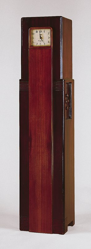 Mahogany radio cabinet in skyscraper form with clock housed in front, radio dials installed on right side and speaker installed in top