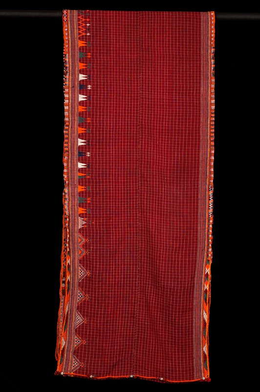 red wool with tan windowpane checks and tan and blue horizontal stripes on both sides; vertical seam decorated with 5 areas of beaded rows and tassels; top and bottom embroidered with bands of various geometric designs; bottom edge has geometric designs above band; two panels stitched down center