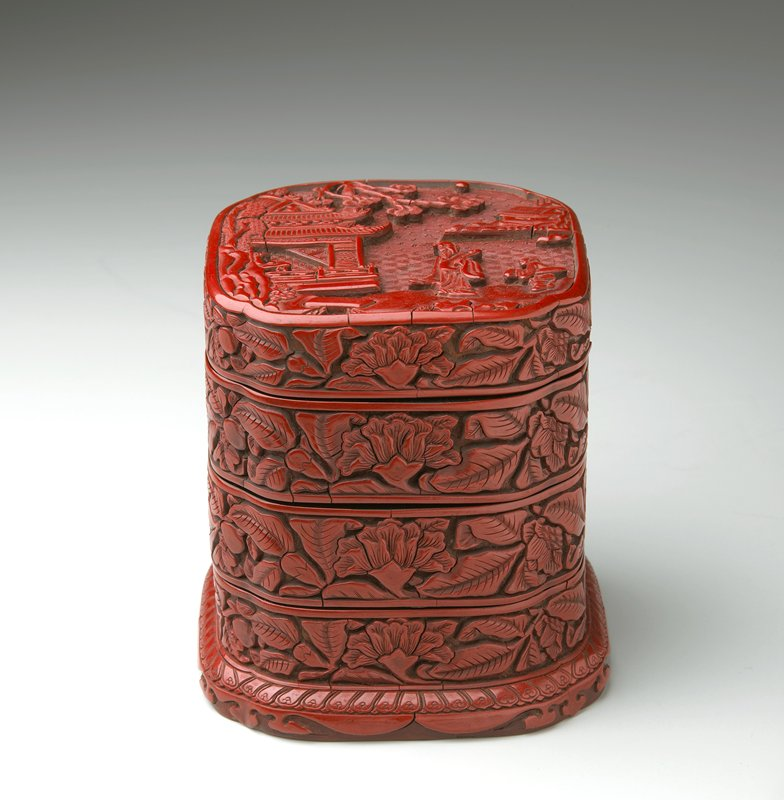 square form with indented corners; lid carved with 2 figures at R in a landscape with buildings at L and UR corner; sides of lid and 3 compartments carved with flowers; base has a raised, sloping foot; red lacquer