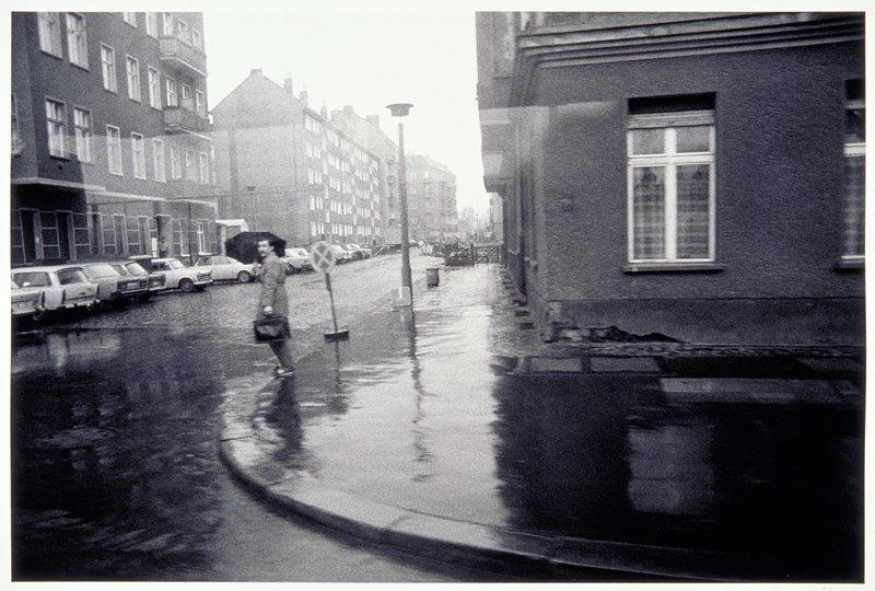 man with umbrella on curb