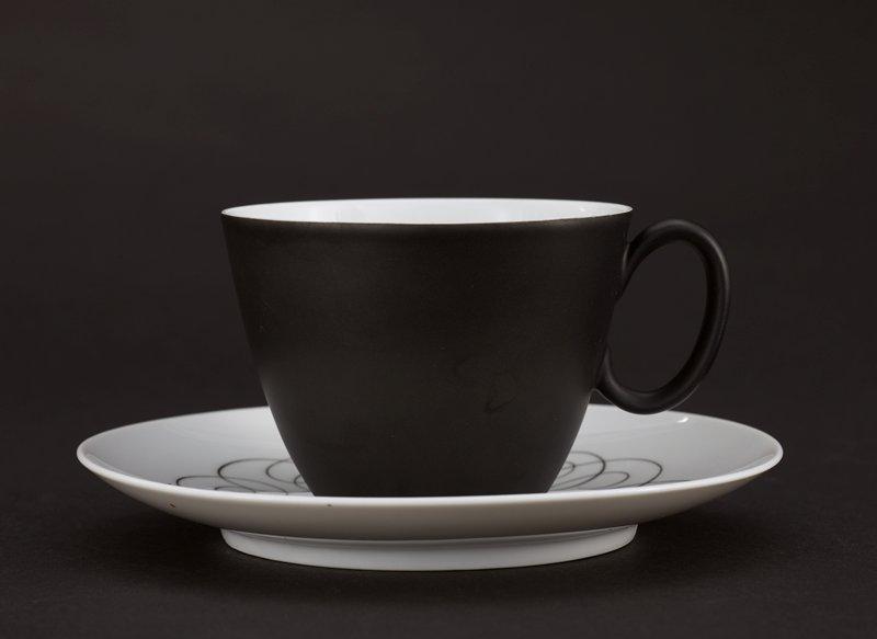 Cup white interior, black exterior; plate white with black script-like design around center