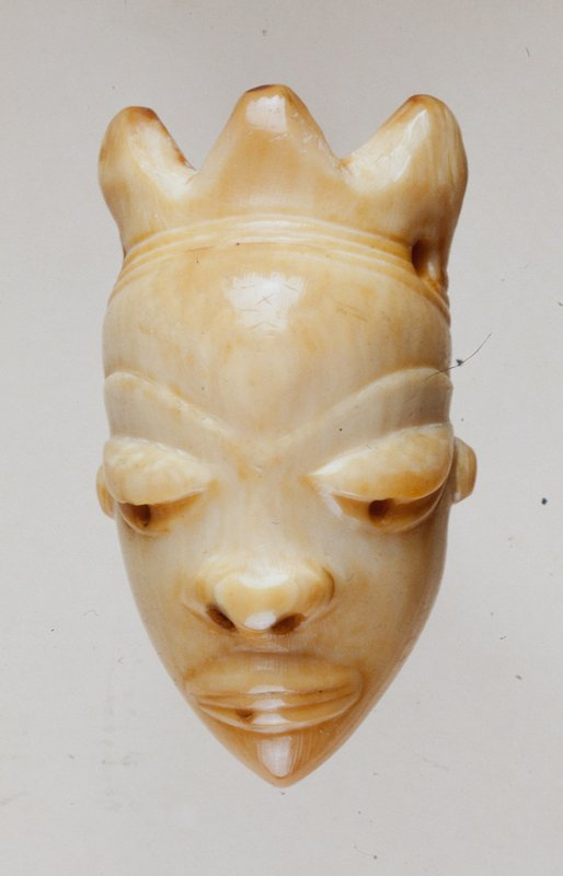Small off-white figure head with three pointed headdress on top. One hole on each end of headdress. Shallow hole for each eye and nostrils.