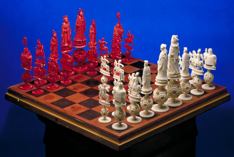 set of 32 chessmen, sixteen red and sixteen white (natural); each chaessman stands on a carved filigree globe, within which are one or more free carved balls; the globe rests on small turned stem, and the foot is carved with double row of lotus design