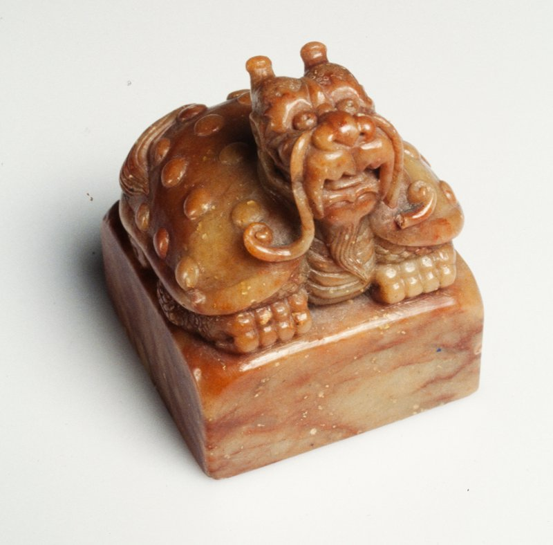 Carved of 'bloodstone,' bowenite with light green/brown ground and heavy striations of 'blood' red. The finial carved in the form of a Divine Tortoise, in whose nature the qualities of the dragon and tortoise are combined, symbolic of a wish for longevity.