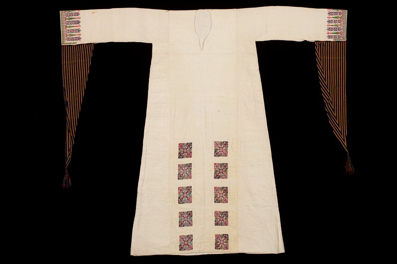 white dress with ten embroidered squares, lower center of front, and embroidered border at cuffs; long triangular extensions to sleeve of blue and gold stripe with tassel at bottom; embroidery in blue, black, green, red