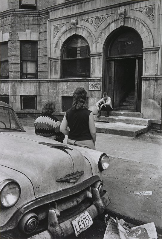 two figures, seen from behind, leaning against the side of a car; figures face a young man sitting on steps in front of an apartment building