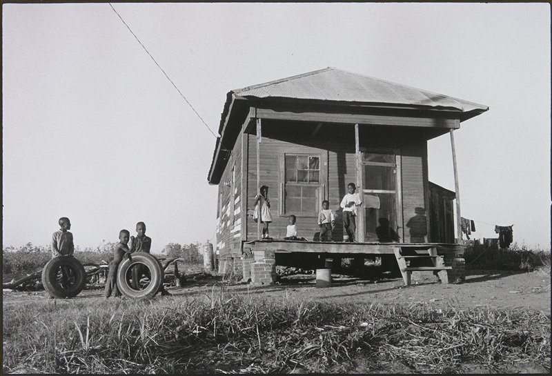 small ramshackle house with corrugated tin roof; four children on porch; three children in yard at left hold up two tires