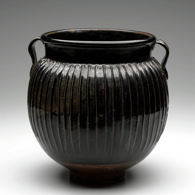 round-bodied jar with wide mouth, on a tall foot; black/brown Temmoku glaze; vertical ribs on body with pair of small handles at mouth, with x's below on body
