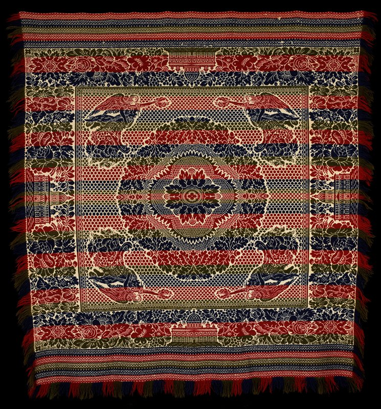 alternating jacquard weave strips in red, blue and green; central floral medallion surrounded by 4 angels; floral and geometric borders with building at center on each side