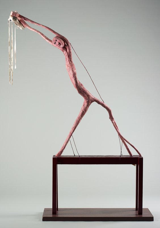 mottled pink figure with elongated body, arms and legs; large stylized hands with downward-facing ballet slippers; small taroon tablelike platform attached to a brown plank base