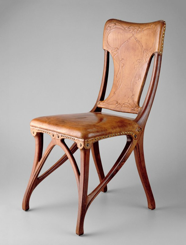 Side chair with embossed leather upholstery. Made for the Dining Room at L'Art Nouveau Bing. The front two legs divide into three pieces, one rising to the center front, one to front corner and the third rises to the join of the seat and back leg and then continues visually, curving slightly upward to the top of the back of the chair. The leather upholstery is tooled in a motif of interlacing flowing ribbons. A separate piece of tooled leather covers the join of the seat and the wooden frame.