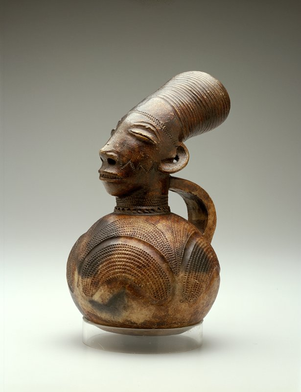 vessel with handle, surmounted by male head; opening of vessel is through top of figure's headdress; surface has glossy appearance; dark clay body