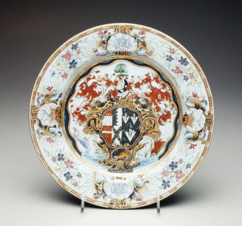 plate decorated with elaborate coat of arms Okeover impaling Nichol, in baroque style; red and white seahorse supporters; border with crested coronets dividing LO monograms