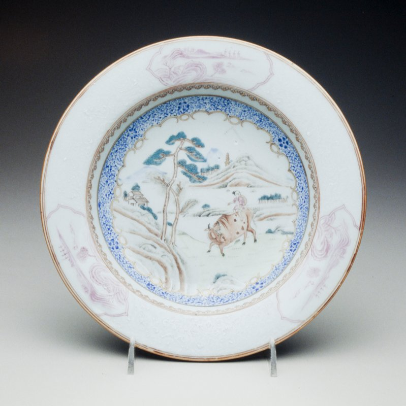 plate decorated with blue, white and bianco-sopra-bianco border of flowers, gilt spearhead inner border, pastoral scene with Chinese boy riding a bull, mountain and trees, border with three cartouche scenes