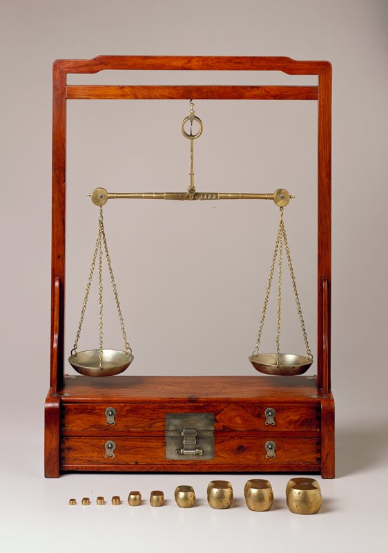 two drawer case with side posts and double cross braces at top, upper most brace hump backed; silver hardware ten brass weights; brass scale with two pans and hanging chains; scale and weights are from a later date than the stand