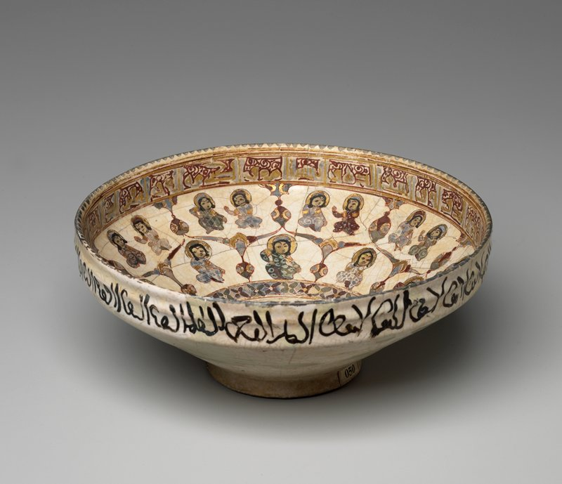 Bowl, Seljuk dynasty, light creamy earthenware, covered with a thick coat of opaque white tin enamel. Funnel-shaped, with straight standing rim, slightly ridged on outside where it is decorated with Cufic characters in black. Low raised foot. Inside of rim decorated with conventionalized band of Cufic characters in gold, blue and red. Medallion in center of bowl shows three figures in blue and gold garments; this medallion is surrounded by ten smaller figures, eahc in a separate 'niche', and above this is a row of sixteen still smaller figures. All figures shown with gold nimbus. Mended; has been broken in many pieces. Saveh excavation.