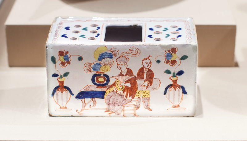 polychrome with chinoiserie design; on top two rows of three holes on either side of large central square opening; with scene of figures in an interior