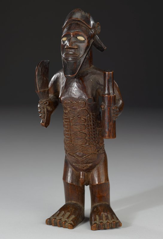 man standing with arm at sides holding a large knife in right and cylindrical object in left; decoratively carved stomach; ivory inset eyes