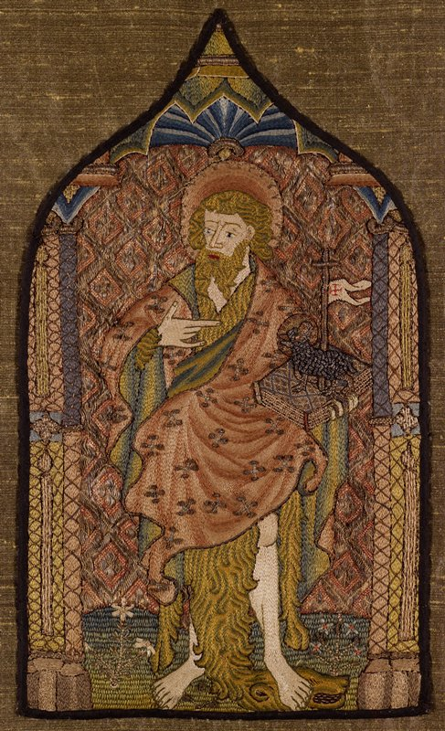 Embroidered panel in the shape of a cathedral window with black border; St. John standing with book in proper left hand; lion's head and skin seen under saint's robe