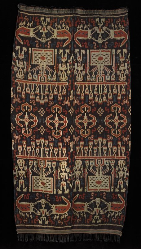 brown ground with ikat design in cream, blue and orange; repeating pattern of 2 alligators flanking a man and 2 men flanking on object with 4 human heads; 2 strips sewn together