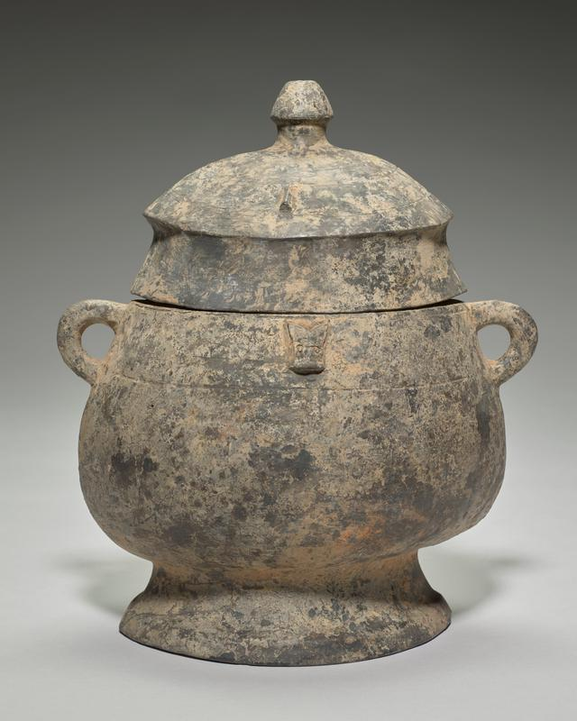 Yu, with cover, of black pottery with small Tao Chi mask on each side. Top of cover, with simple knob finial, decorated with incised lines and two minute portruding wedge-shaped bosses; coating of clay on inside and thin deposit on outside.