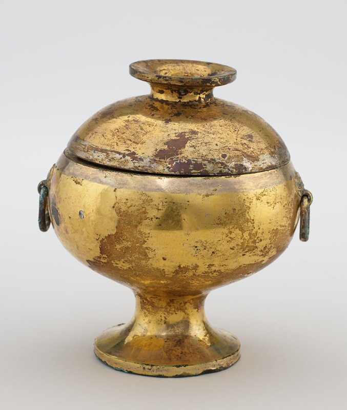 Ritual urn, Tou form; two ring handles attached to body of vessel with an elephant head (?) motif. Trumpet base, truncated trumpet finial. The bronze was lightly covered with silver before being washed with gold. Gold has worn off in spots revealing silver green iridescence; corrosion advanced to such a stage that handles have become attached to body of urn. Tou belong to the yi class, and were used to contain grain offered to the dead. Excavated, with other objects, rom a tomb in Honan, 1929. N.B.similar piece in Grenville Winthrop Collection, New York