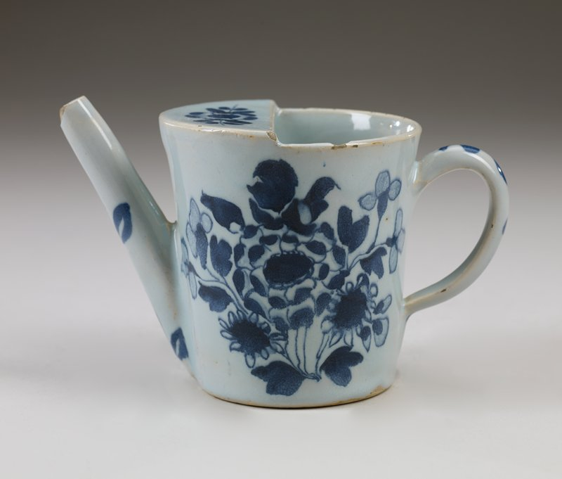 ceramic feeding cup, blue and white with floral design, handle and long spout, half of top is carved