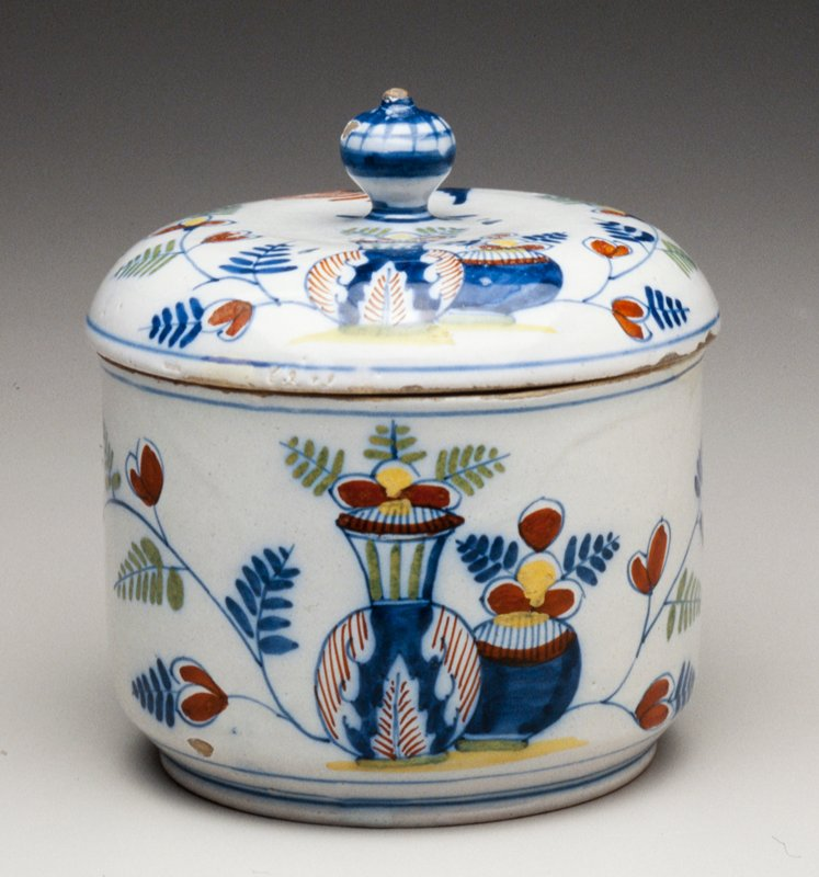 ceramic covered sugar pot; blue and white with addition of green, yellow and red; design of two vases with flowers opposed by a flying bird