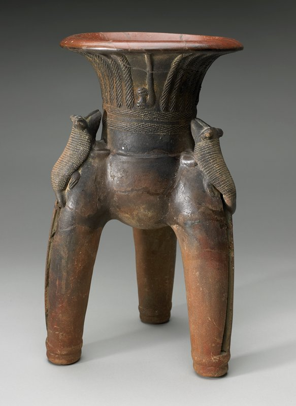 Tripod vessel that is flared at the top, at the top of each leg is what appears to be armadillo; vertical slit in each leg that are hollowed out with rattles placed inside; incised on the top.