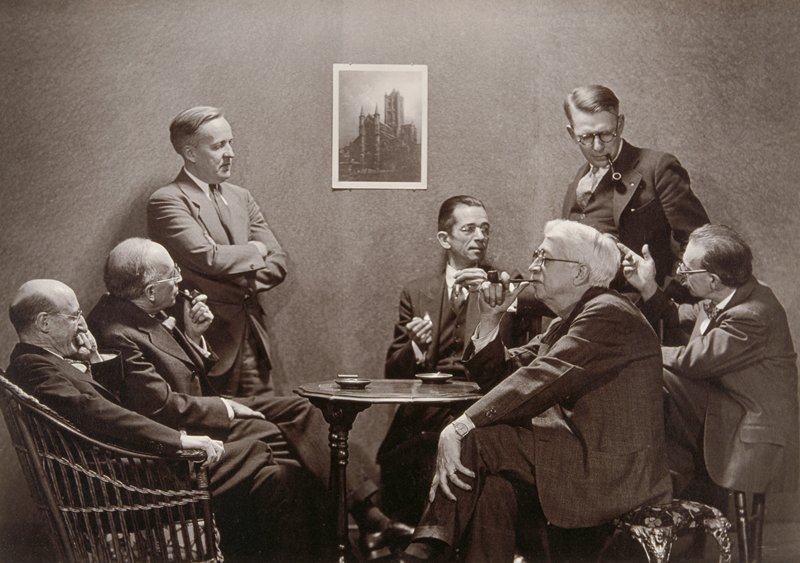 image of seven men in suits, five seated, two standing around table with image of cathedral on wall