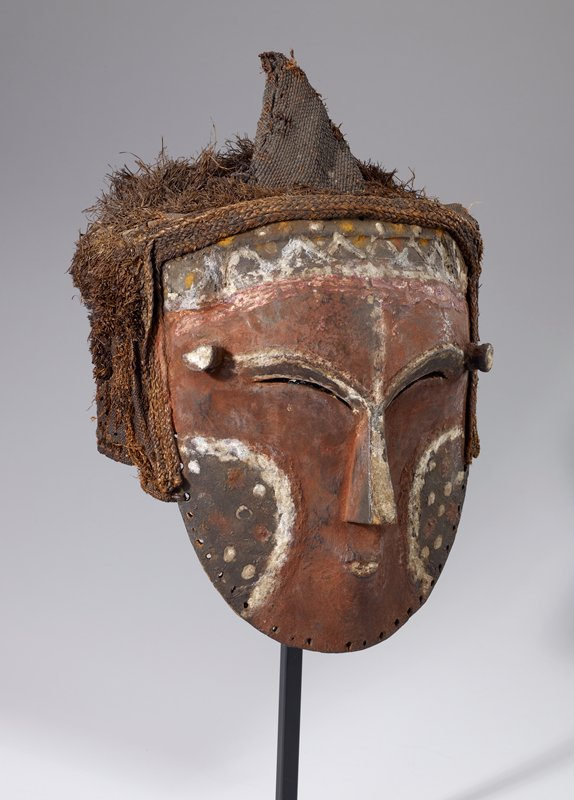 round red face with white and brown marks on cheeks and forehead; 2 protrusions on temples; head covered with tufted cloth