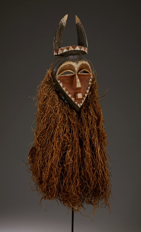 small face with pointed jaw, square mouth, triangular nose, slit eyes and headdress with horns; long raffia beard; salmon, white and brown pigment on face