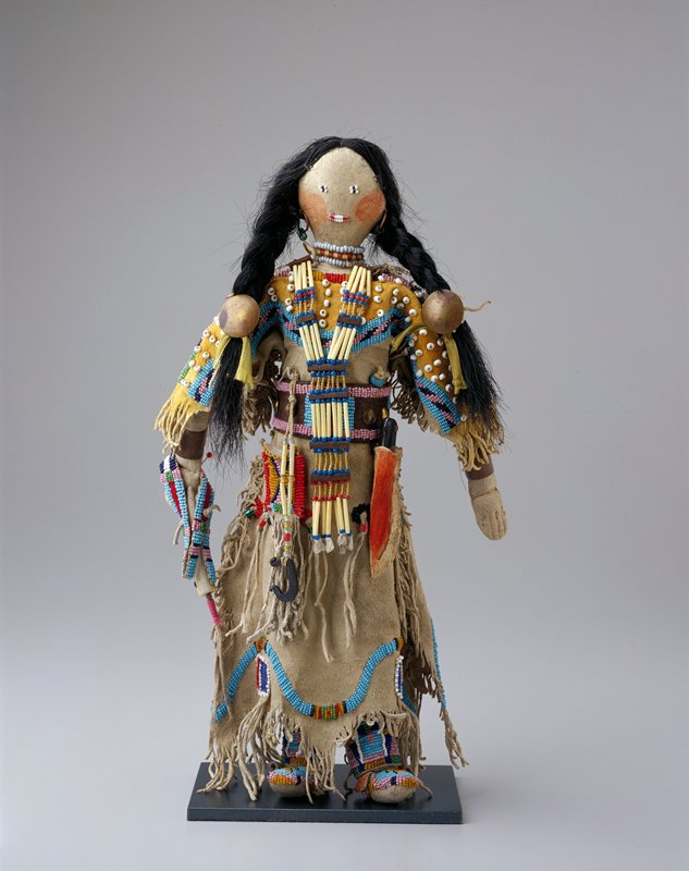 hair in two braids tied with ribbons, hide cords and metal disks; wearing hide dress with fringe and beads, beaded leggings and beaded moccasins; metal bracelet on each wrist, metal hoop earrings with green beads, beaded choker necklace and longer beaded necklace hanging below waist; stiff leather belt with knife sheath (and removable knife) and fringed pouch; bone tool with beaded cover pinned to proper right hand; beaded facial features