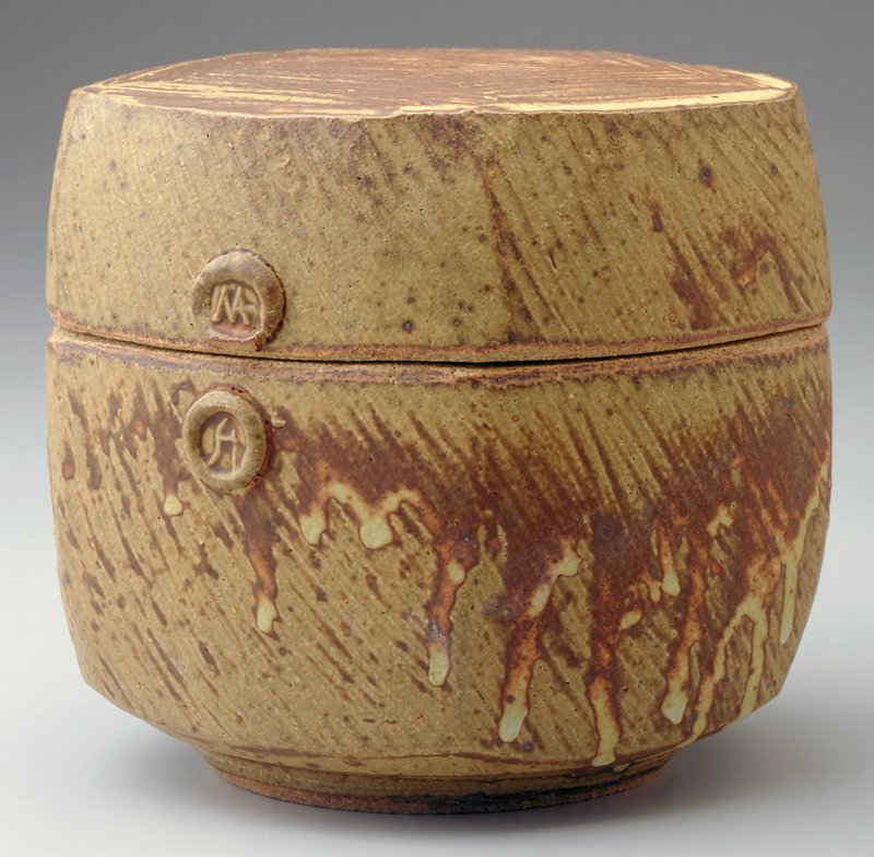hexagonal shaped box with rounded corners; 2 small buttonlike seals, on lid and base, on one side; brown and tan slightly dripped glaze