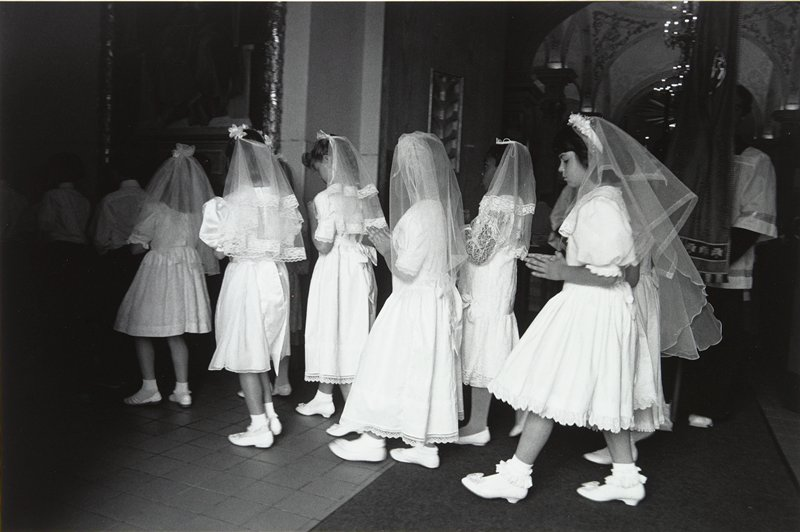 black and white photo of six young girls in white dresses and veils in procession