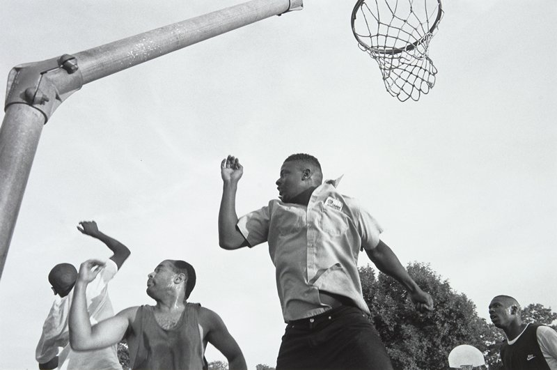 black and white photo of four black men under basketball hoop