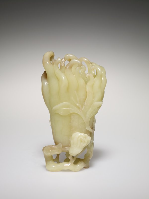 Finger citron of yellow jade; around body and base of vase a pattern of twining leaves and a smaller finger citron in relief. Teakwood stand.