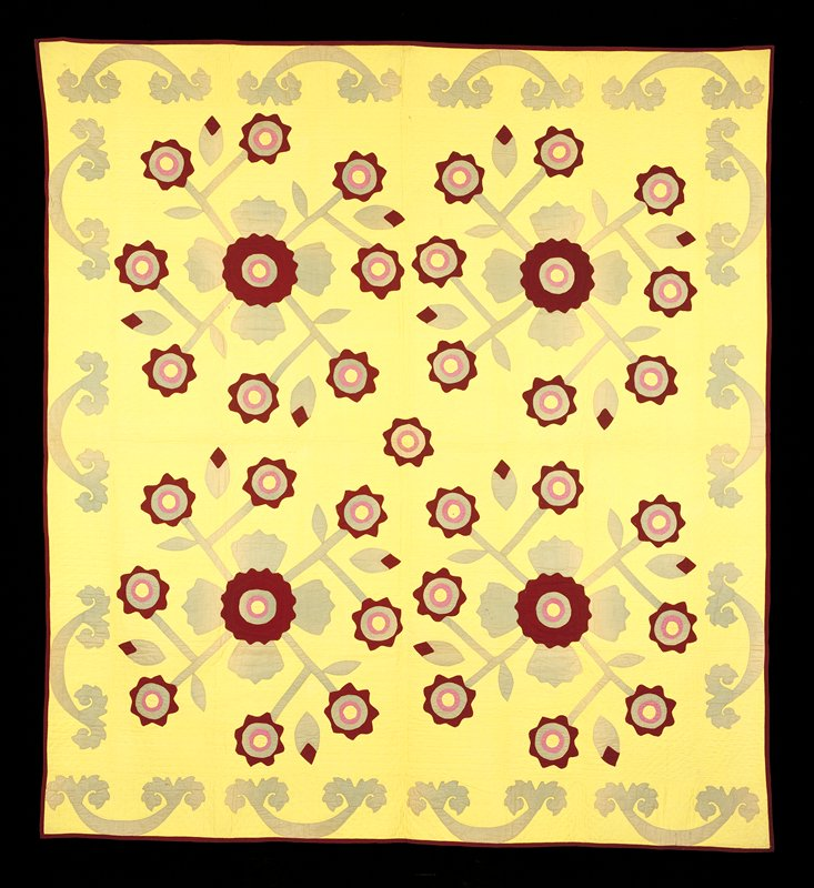 Yellow background; leaf-like applique border in green; 4 large appliqued floral medallions in green, maroon, pink and yellow; tan and red vine print backing