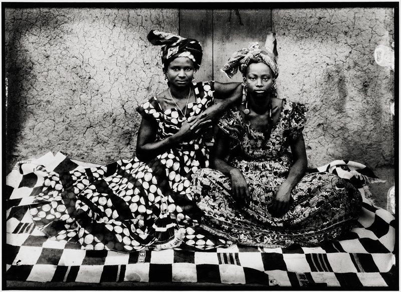 "two female friends seated and dressed in loose 'grand Dakar' dresses, one in a flower print and the other with large white spots within banding Two friends dressed in loose ""grand Dakar"" dresses, one in a flower print, and the other with large white spots known as ""petites pièces d'un franc"" (tama-tama ni)."