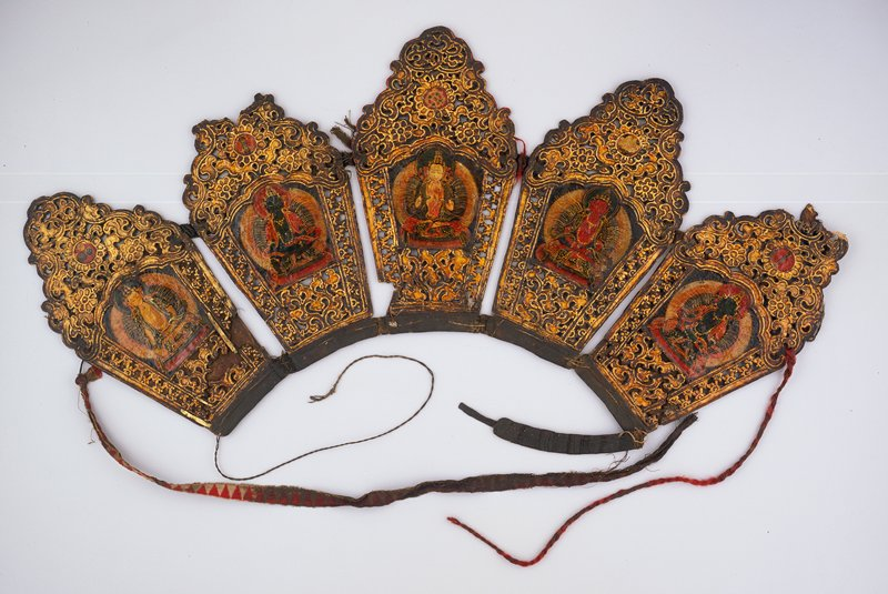 headdress consisting of five sections attached together with leather bands; openwork decorations on each section decorated with one of the five dhyani bodhisattvas; above each figure is a roundel bearing a sacred emblem such a three jewels, crossed 'vajras,' the wheel of the law, the lotus and the sword
