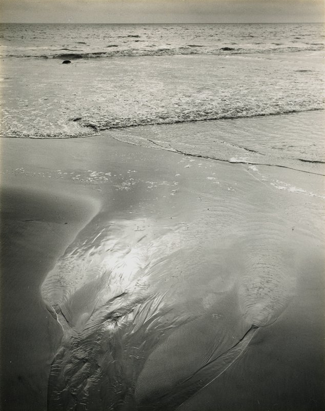 rippled patterns in wet sand from tide in foreground, with small breaking waves in background