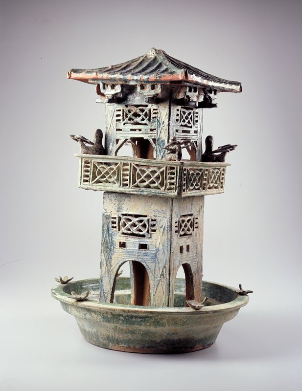 green tower in two parts; top with archer in each corner; base=moat in bowl with fish and frogs; swans on rim