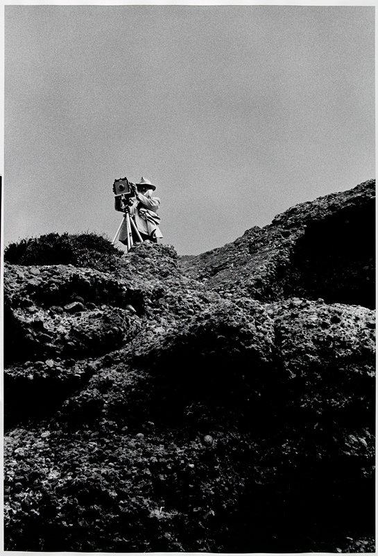 man wearing a hat and coat, standing behind a boxy camera on a tripod, on top of rock formation