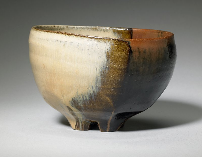faceted base and crosscut feet; slightly flattened at rim on one side; brown glaze on one side, tan on other side